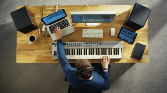 Top View of a Musician Creating Music at His Studio, Playing on a Musical Keyboard. His Studio is Sunny and Pleasant Looking. video