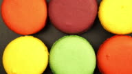 TRACKING: Top view of a Rows of Colorful Macaroons on a black table video
