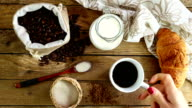 Top view of breakfast scene with cup of coffee, coffee beans, milk and croissant, female hand putting a cup of coffee video