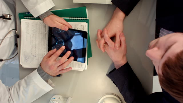 Top view of Doctor reviewing x-ray with patient video