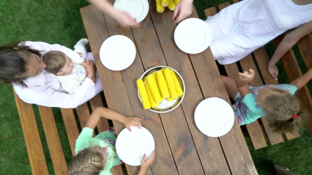 Top view of family enjoying an outdoor dinner eating boiled corn on the cob video