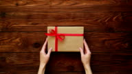 Top view of hands adjusting a present box video