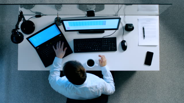 Top View of IT Specialist Working with Spreadsheets and Documents on His Laptop and Personal Computer Simultaneously. Stack of Signed Papers on His Desk. video