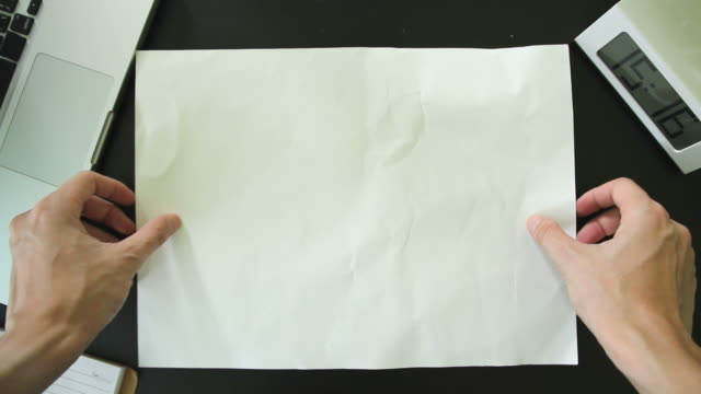 Top view of Male hands putting a blank white sheet on the office desk. video