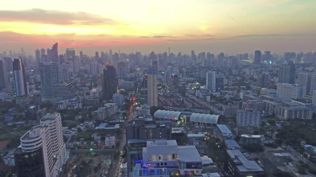 Top view of skyscraper which sunset Golden light though clouds over cityscape, video