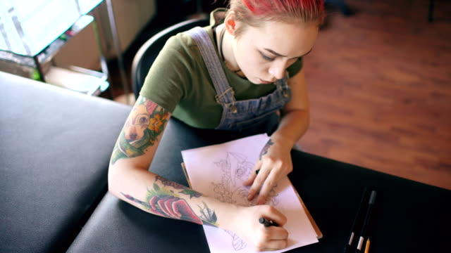 Top view of young attractive red haired woman tattoo artist sitting at table and creating sketch for tattooing in studio indoors video