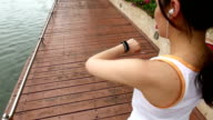 Top view of young woman run and looking wear smart watch device video