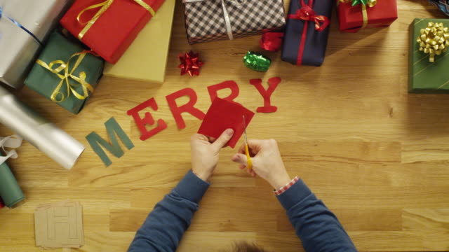 Top View Time-Lapse of a Man Cutting Letters for Words 'Merry Christmas' and laying Them on The Wooden Table With Gift Wrapped Boxes. video