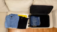 Top view timelapse of packing clothes into a suitcase video