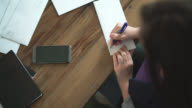 Top view to the workplace. Young woman writing the letter. video