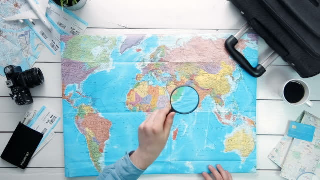 Top view traveler's hands looking at world map using magnifying glass at white wooden desk video