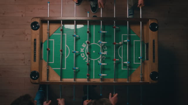 Top-shot of guys playing tabletop soccer in apartment video