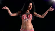 Torso of a beautiful young girl belly dancer on a black, back light, cam moves down, slow motion video