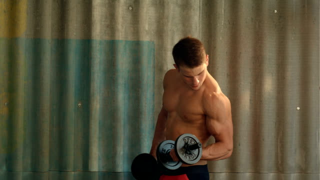 Torso shot of a young man with bare chest lifting dumbbells video