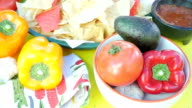 Tortilla chips and salsa on table with fresh peppers, tomatoes, and other Mexican cuisine ingredients. video