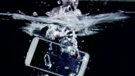 Touchscreen smart phone with incoming call on display falling in water video