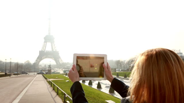 Tourist at the Eiffel tower using digital tablet video
