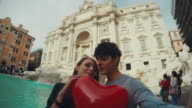 Tourist couple taking a selfie at Trevi fountain with heart video