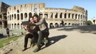 Tourist couple taking a selfie in front of the Coliseum video