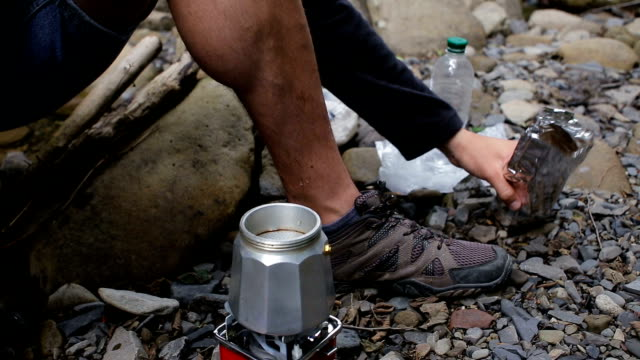 A tourist guy pours coffee into a coffee maker in a campsite on the river bank video