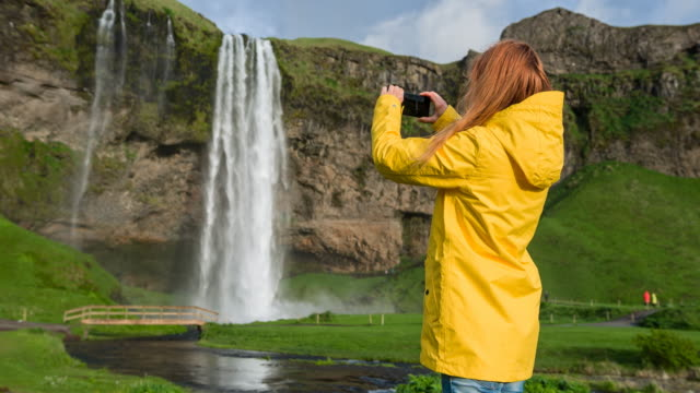 Tourist in Iceland taking pictures of Seljalandsfoss waterfall video