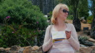 A tourist looks at a map of the area and a mobile phone. It defines your location video