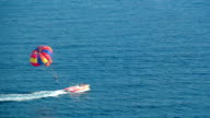 Tourist on a colorful parachute towed by a boat. video