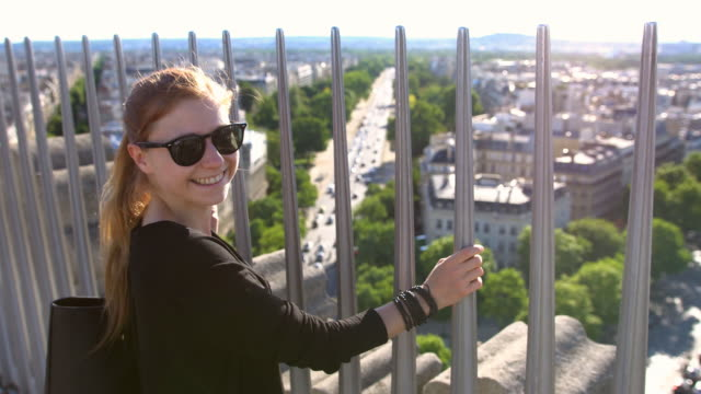Tourist on top of Arc de Triomphe in Paris overlooking the city, smiling into camera video