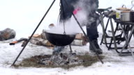 Tourist people cook in pot hanging over campfire fire in winter. FullHD video