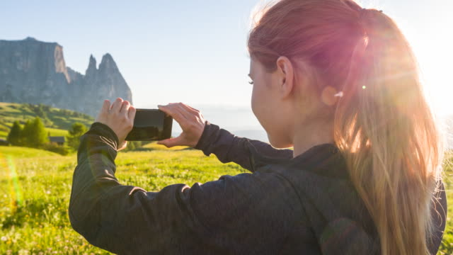 Tourist photographing blooming meadows with mountains in background video