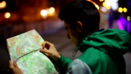 Tourist searching place location in map, lost city night video