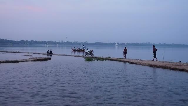 Tourist sitting on boat to watch sunset in U-Bein bridge video