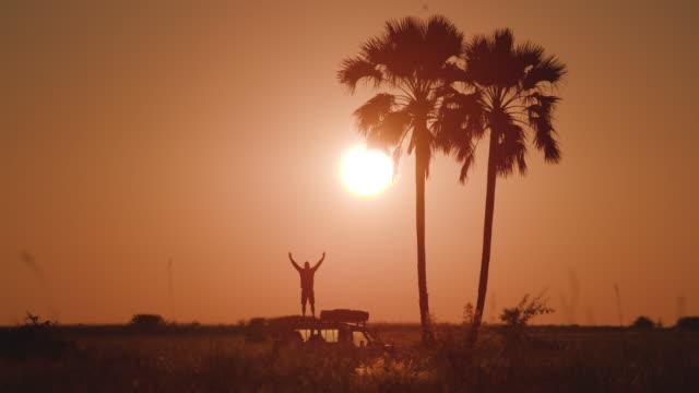 Tourist standing on 4x4 roof taking in beautiful sunset of Okavango Delta video
