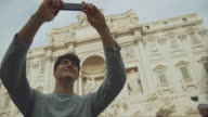 Tourist taking a selfie in front of Trevi fountain in  Rome video