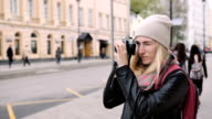 Tourist taking photo of old street at the retro film camera video