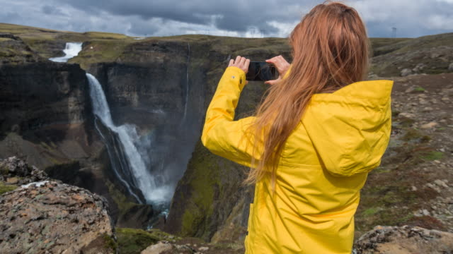 Tourist taking pictures of Iceland's canyons and waterfalls video