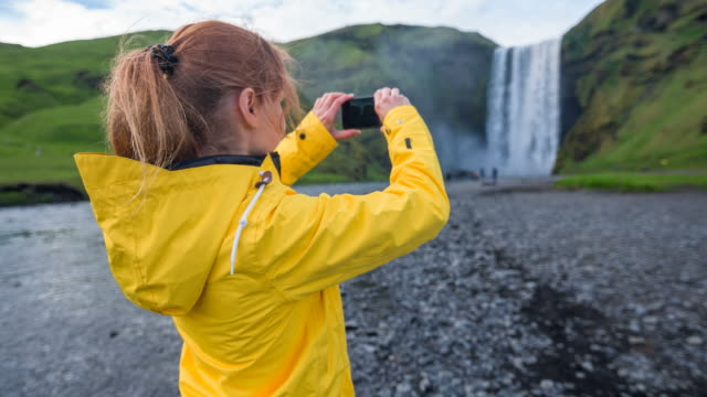 Tourist taking pictures of Iceland's waterfall Skogafoss video