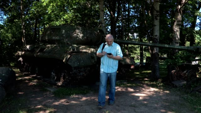 Tourist using tablet at the tank of the second world war video