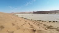 Tourist walking in the majestic Namib desert, Sossusvlei, Namib Naukluft National Park, main visitor attraction and travel destination in Namibia. Adventures in Africa. video