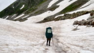 tourist with Hiking backpacks coming down the High Snowy Mountains in Kavkaz region video
