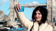 tourist woman is making a selfie with London Tower bridge in background video