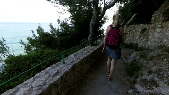Tourist woman travels to mediterranean country at spring season. Girl walk the stone road path with the sea on a backgorund video