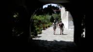 Tourists entering monastery through an arc video