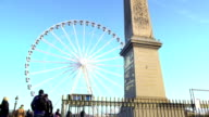 Tourists looking at high Egyptian Luxor Obelisk, huge observation wheel in Paris video