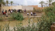 Tourists near the Sacred water of the River Jordan. River where Jesus of Nazareth was baptized by John the Baptist. The border between Jordan and Israel. video