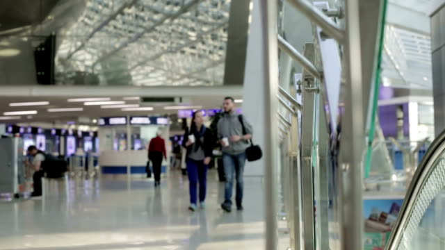 Tourists walk through the airport passing by the information board. video