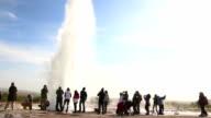Tourists watching the Strokkur geyser eruption in Iceland at dusk video