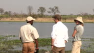 Tourists with safari guide looking at hippo in the water,Botswana video