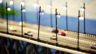 Toy bridge with cars stand, train and barge under it. video
