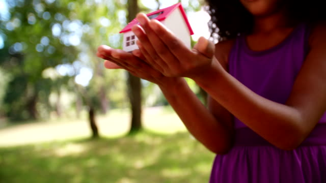 Toy house with solar cell being held by Afro girl video